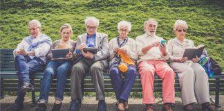 Personas mayores en un banco con moviles